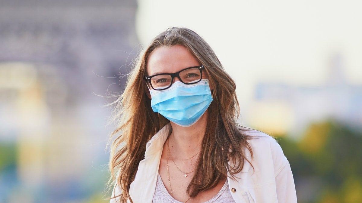 Eine junge Frau mit Schutzmaske vor dem Eiffelturm in Paris.. © Ekaterina Pokrovsky/Shutterstock.com