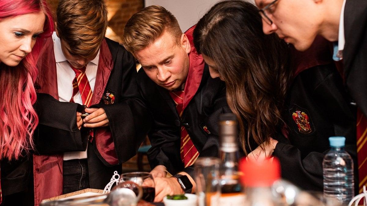 Leidenschaftliche Harry-Potter-Fans perfektionieren ihre Party mit ikonischen Gryffindor-Umhängen.. © Ekaterina Soldatenko/Shutterstock.com