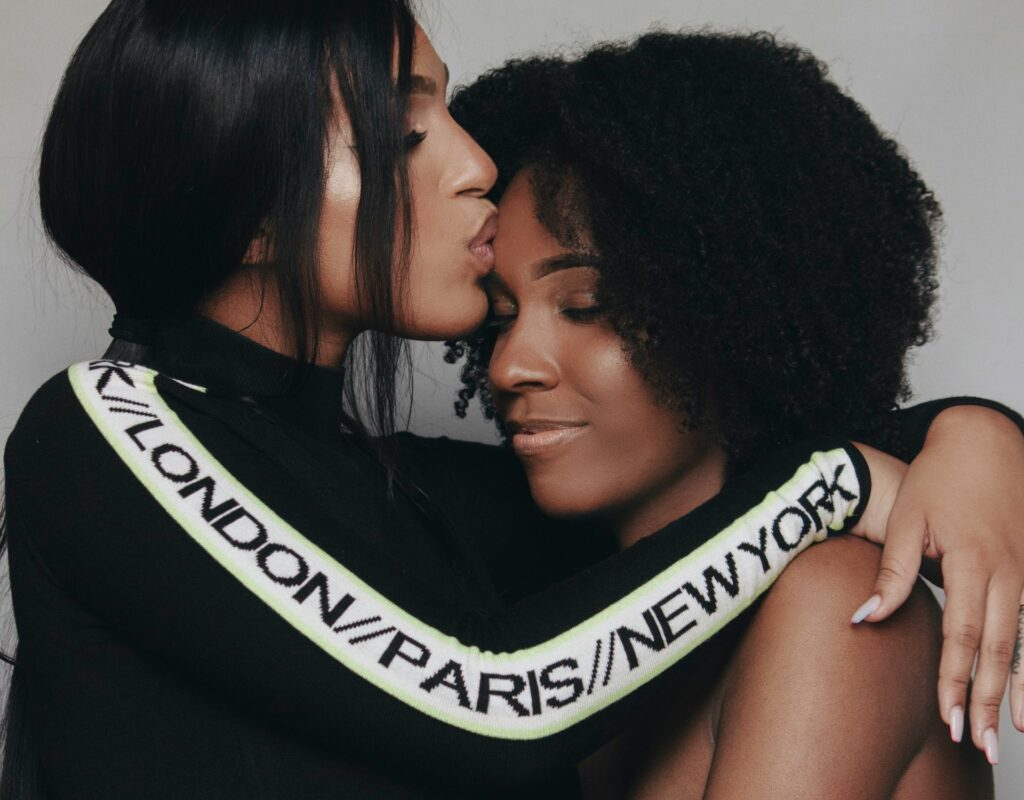 Zwei Frauen, die sich umarmen. Eine gibt ein Kuss auf die Stirn.