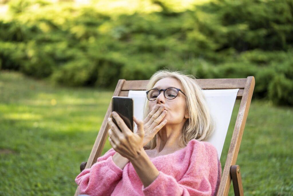 ältere Frau versendet einen Luftkuss per Smartphone