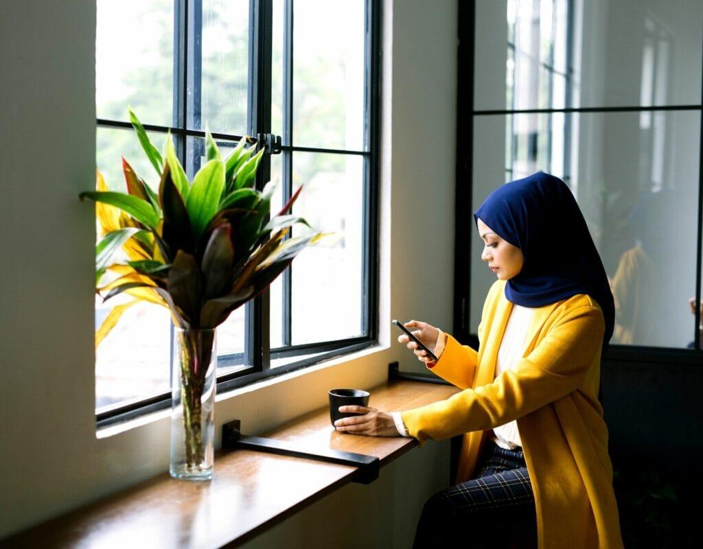 frau mit hijab im cafe mit smartphone