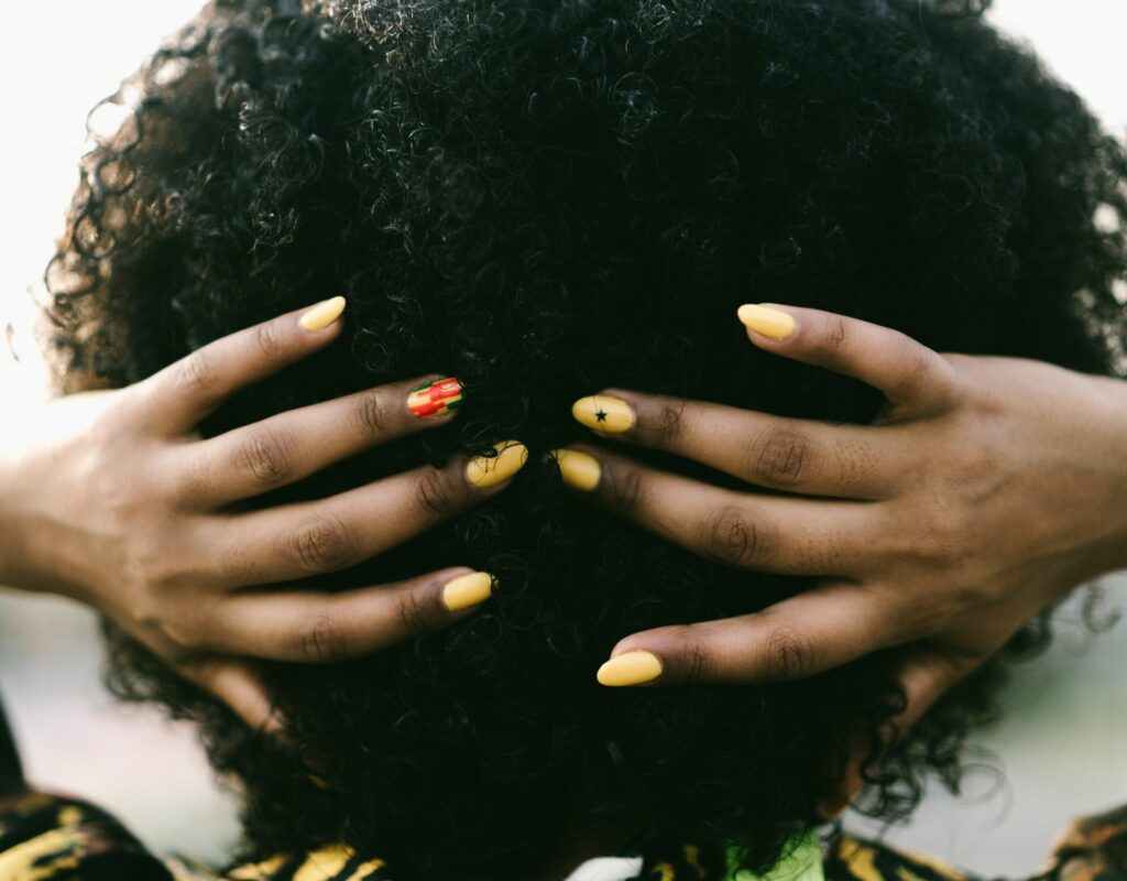 Frau mit gelbem Nagellack
