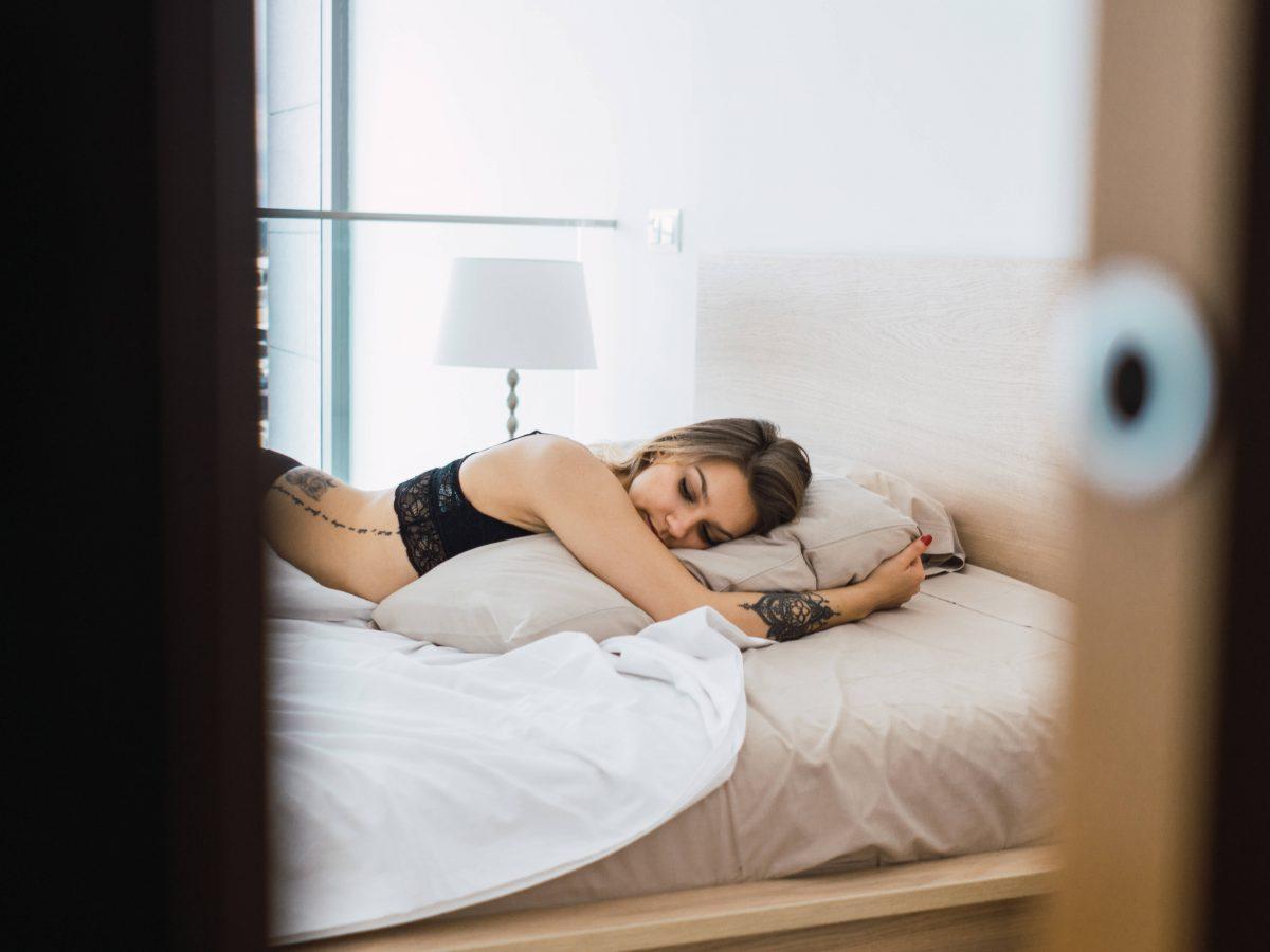 Frau im Bett bei offener Schlafzimmertür